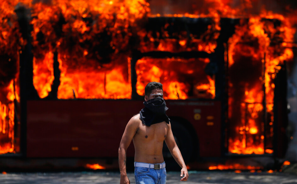 An anti-government protester walks near a bus that was set on fire by opponents of Venezuela's President Nicolas Maduro during clashes between rebel and loyalist soldiers in Caracas, Venezuela, Tuesday, April 30, 2019.