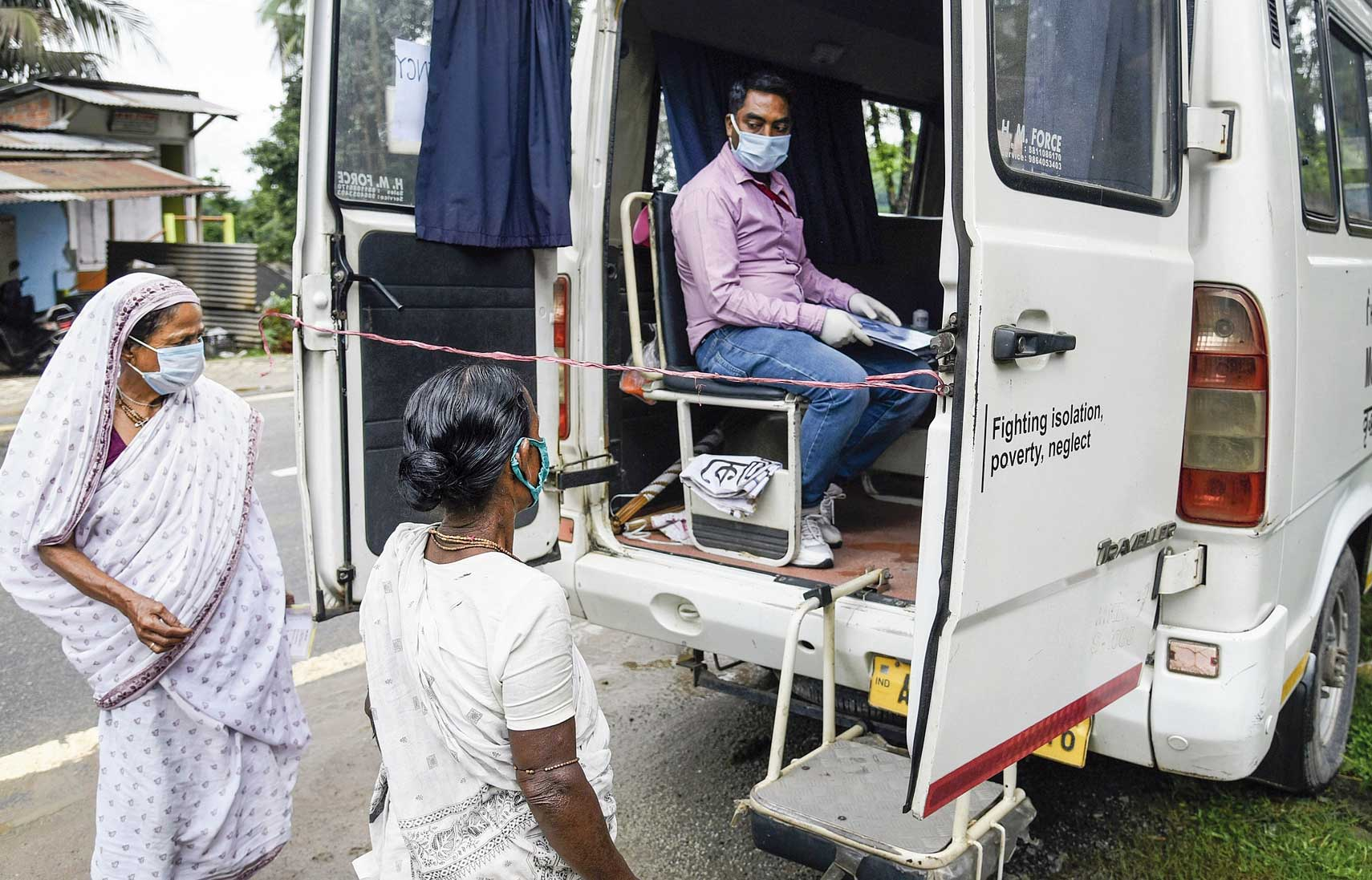 Elderly women speak to a health worker sitting inside a mobile medical van at Panikhaiti in Assam's Kamrup district on Wednesday.