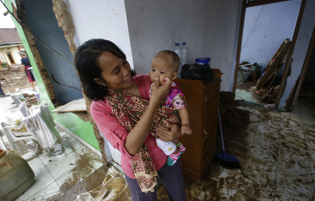 A woman holds her baby inside a destroyed house in Carita, Indonesia, on Thursday.