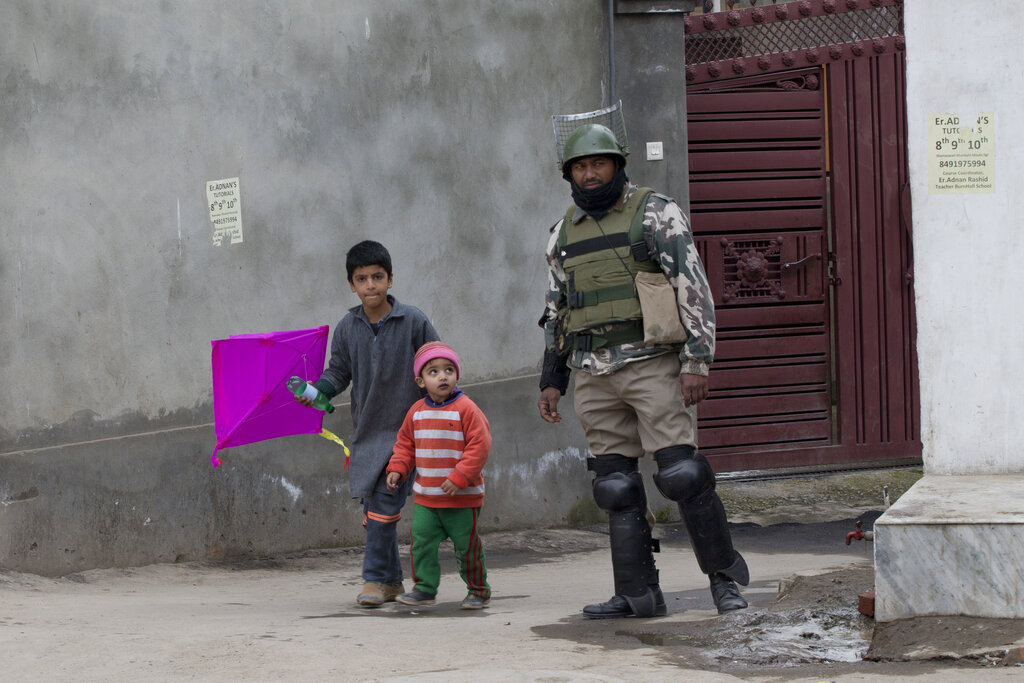 Children walk past a soldier during a security lockdown in Srinagar on Friday.