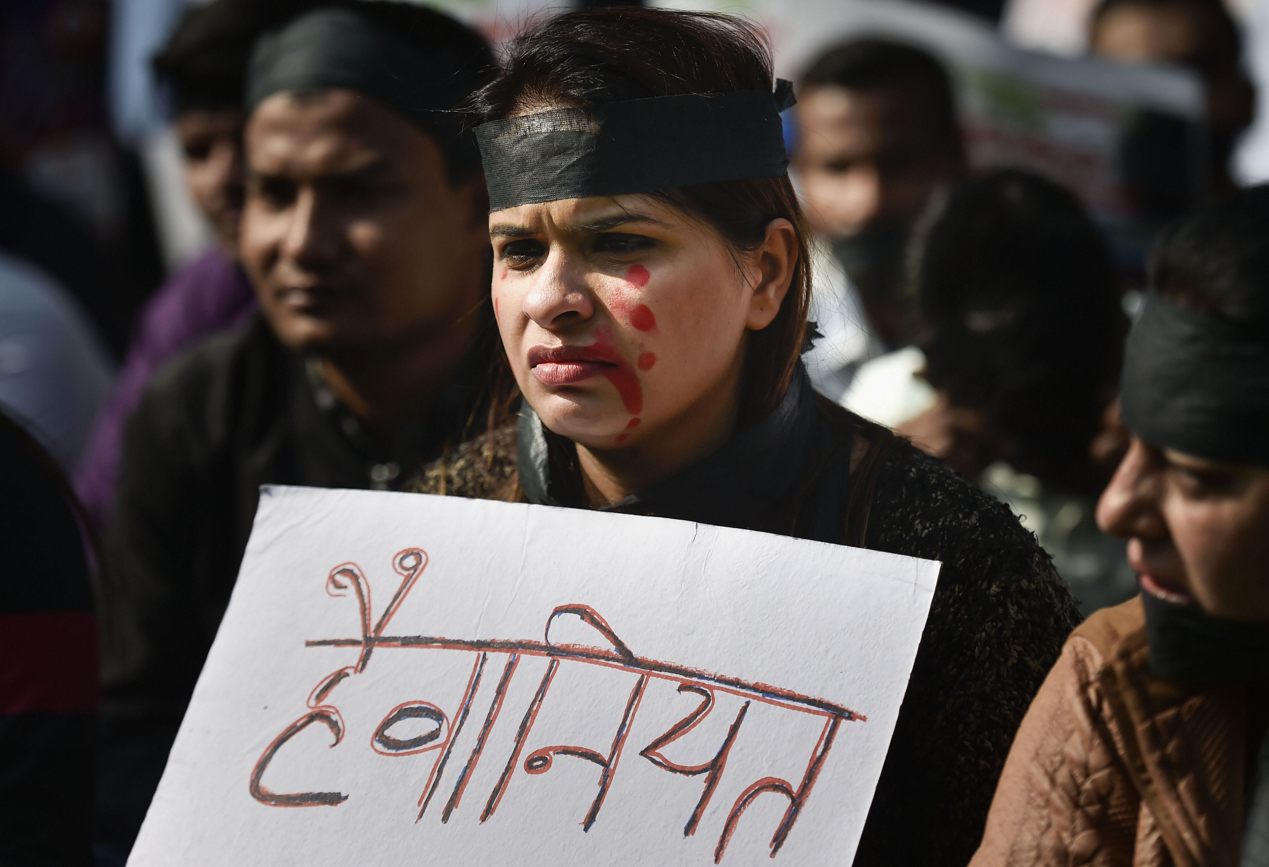 A member of National Students Union of India (NSUI), wearing a black band, holds a placard during a protest against the rape and murder of a veterinarian in Hyderabad last week, in New Delhi, Monday, December 2, 2019.
