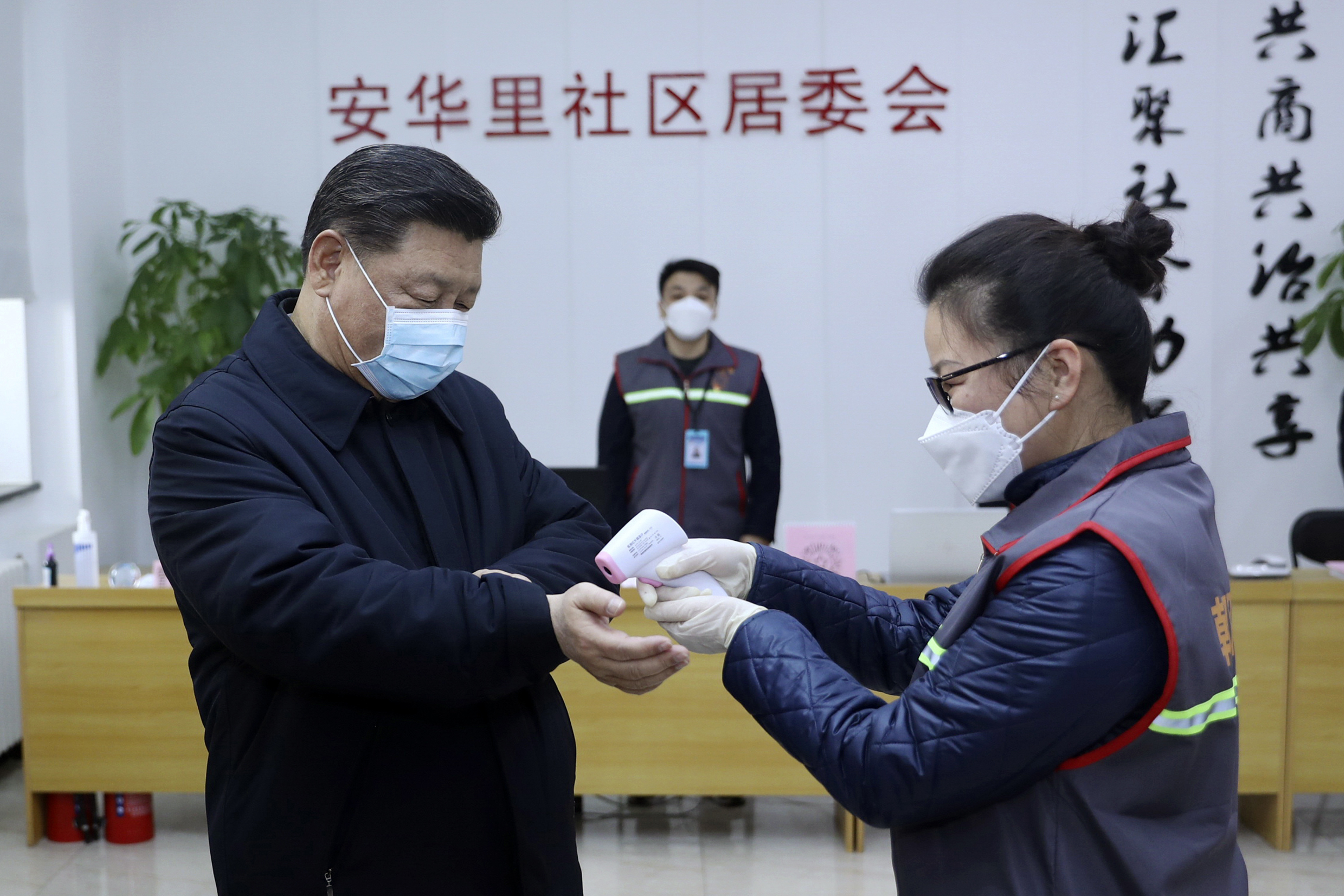 Xi Jinping (left) wearing a protective face mask, receives a temperature check as he visits a community health center in Beijing on Monday