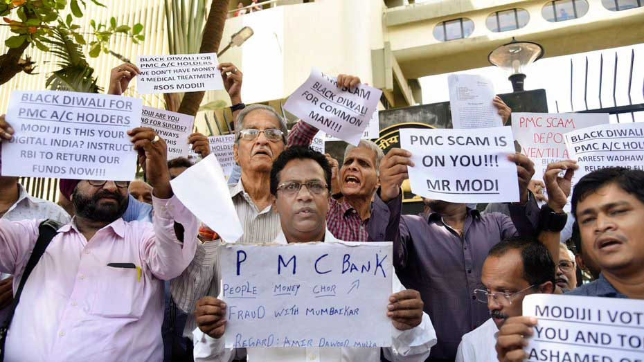 Depositors of Punjab and Maharashtra Cooperative (PMC) bank display placards during a protest over the bank's crisis, outside the Reserve Bank of India building, in Mumbai, on October 1, 2019.