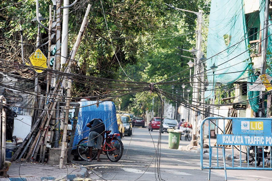 A mesh of snapped wires hangs over a south Calcutta road days after Cyclone Amphan struck the city