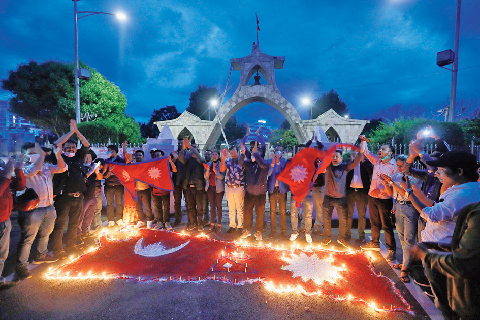 People light candles on an outline of the new map of Nepal drawn on a road as they celebrate in Kathmandu on Saturday.