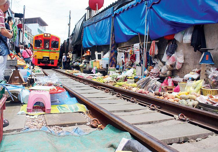 Trains pass through the Maeklong Railway Market eight times a day