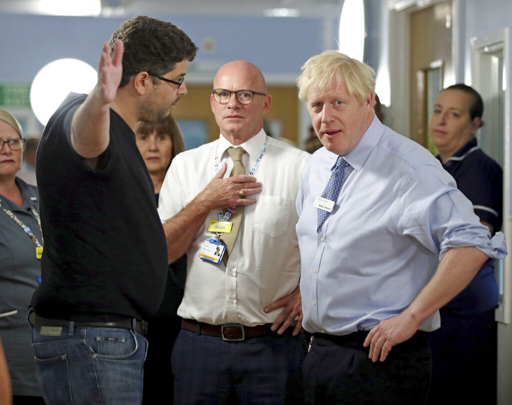 "British Prime Minister Boris Johnson (right) listens to Omar Salem (left), the father of a sick child, during a visit to the Whipps Cross University Hospital in east London on Wednesday. Salem said the care his child received had not been acceptable. ""That's just not acceptable,"" Salem told Johnson."