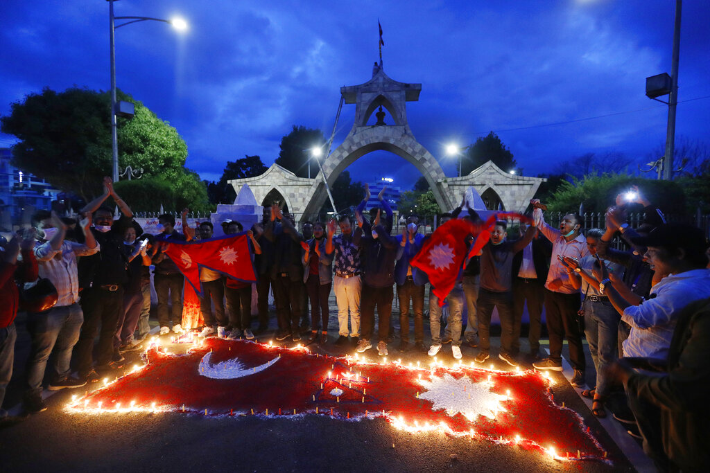 People light candles on an outline of the new map of Nepal drawn on a road as they celebrate the approval of the political map to include territory claimed by both the country and India in Kathmandu on June 13