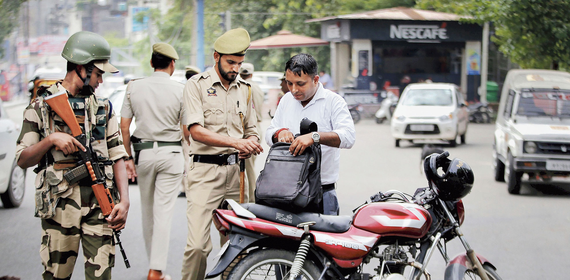 A policeman inspects the bag of a motorcyclist during a security check in Jammu on Tuesday.