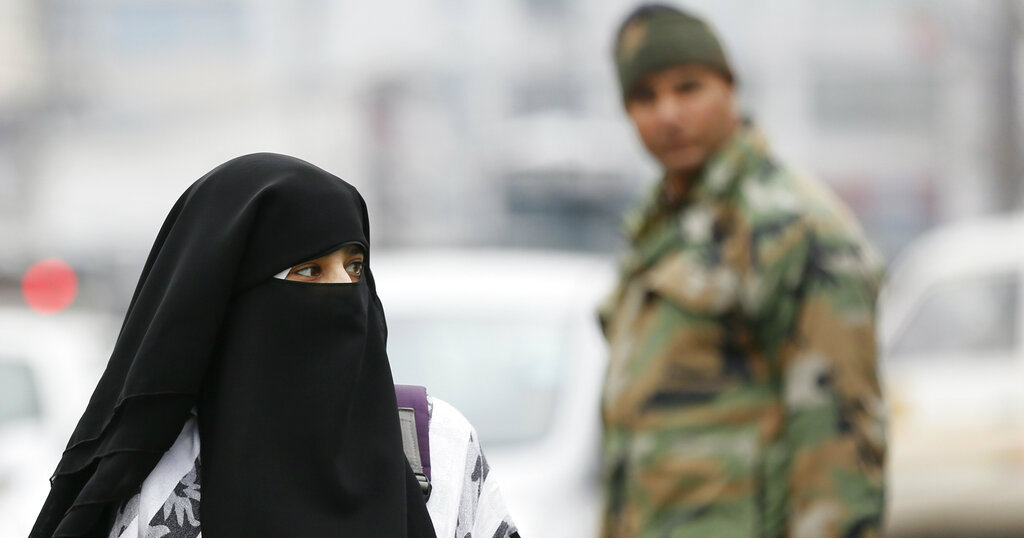 A Kashmiri woman walks near an explosion site in Srinagar on Thursday as a paramilitary trooper stands by.