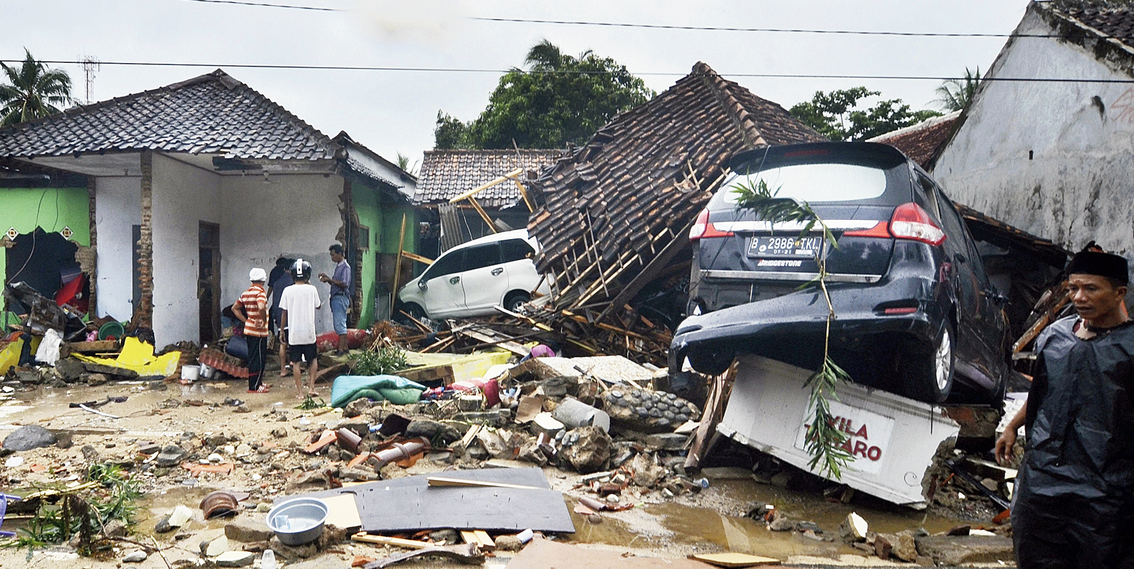 Houses and cars lie in a mangled heap in the aftermath of the tsunami at Carita, Indonesia, on Sunday.