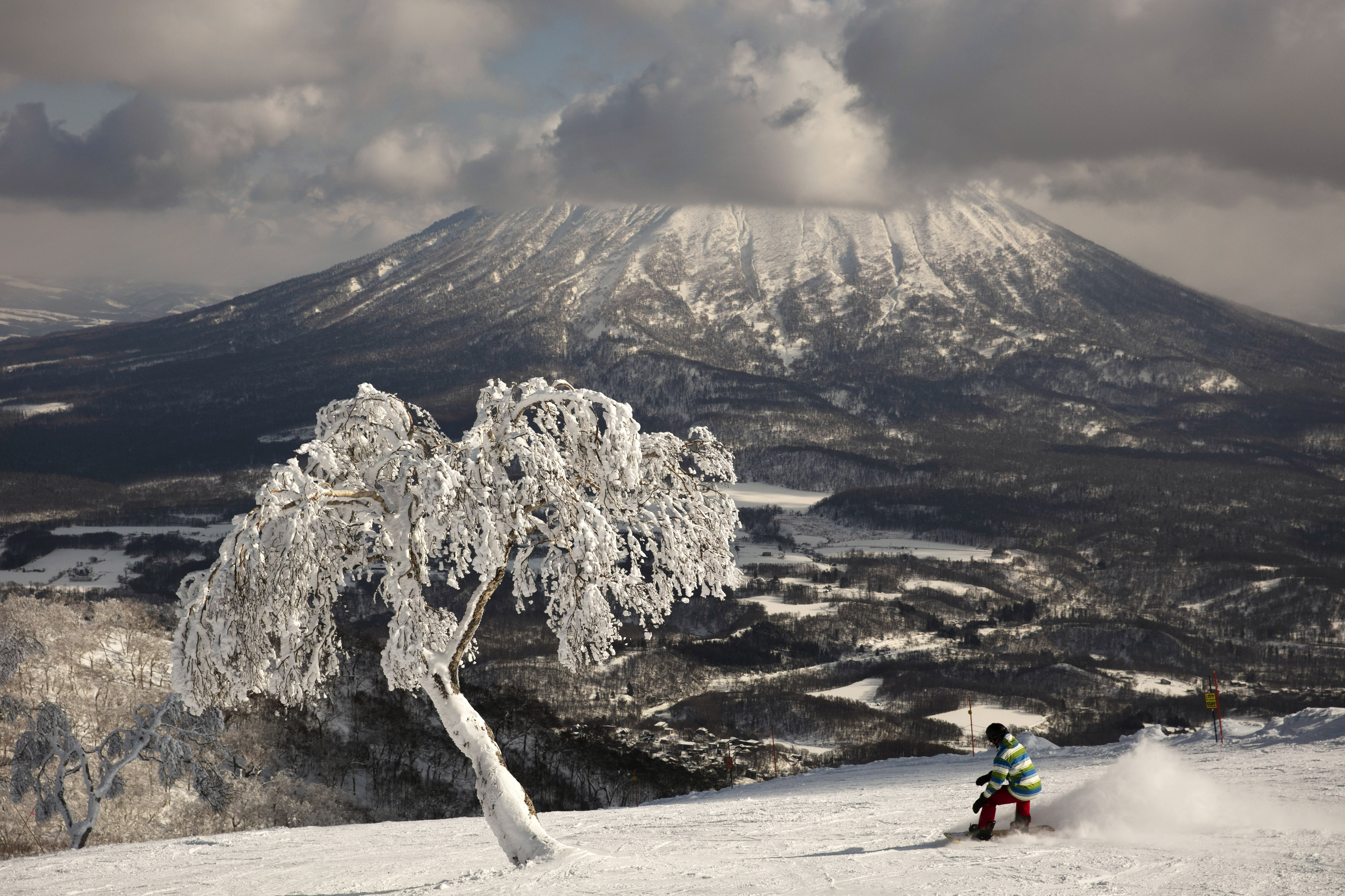 "A man snowboards down a slope overlooking Mount Yotei at a ski resort Feb. 5, 2020, in Niseko, Hokkaido, Japan. ""There's a lot less snow,"" said Nguyen Nguyen, a skier visiting from Hong Kong. ""This is definitely the worst I've ever seen it."""