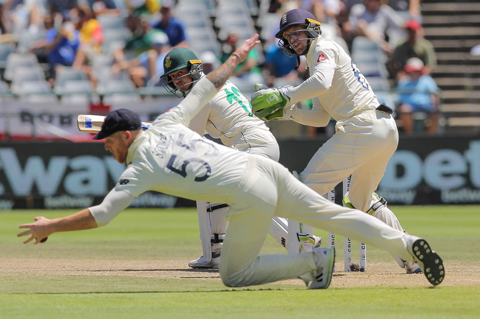 England's Ben Stokes fields the ball while England's wicketkeeper Jos Buttler and South Africa's batsman Quinton De Kock watches on during day five of the second cricket test between South Africa and England at the Newlands Cricket Stadium in Cape Town, South Africa on Tuesday