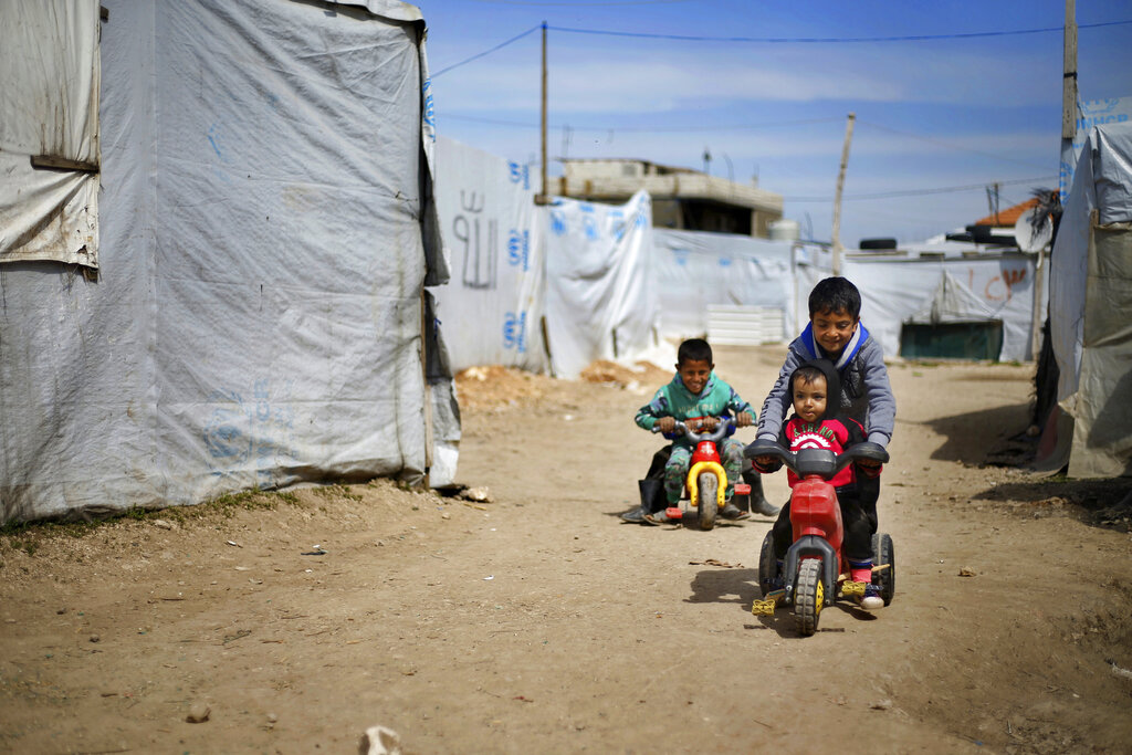 Syrian displaced children play outside their family tents at a Syrian refugee camp in the town of Bar Elias, in Lebanon's Bekaa Valley.
