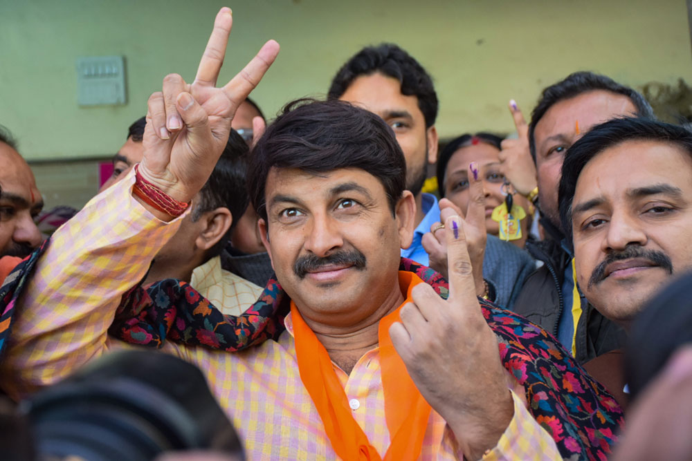 Delhi BJP President Manoj Tiwari shows his finger marked with indelible ink after casting vote during the Delhi Assembly election, in New Delhi