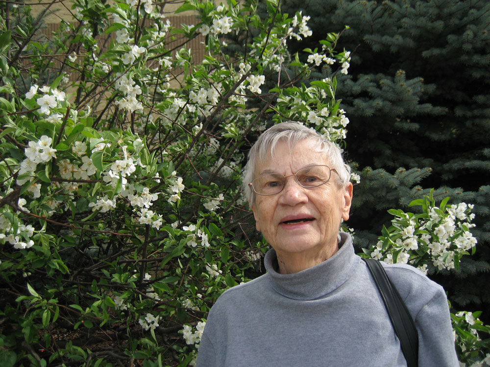 Dorothy by a flowering tree on the bank of Lake Monona