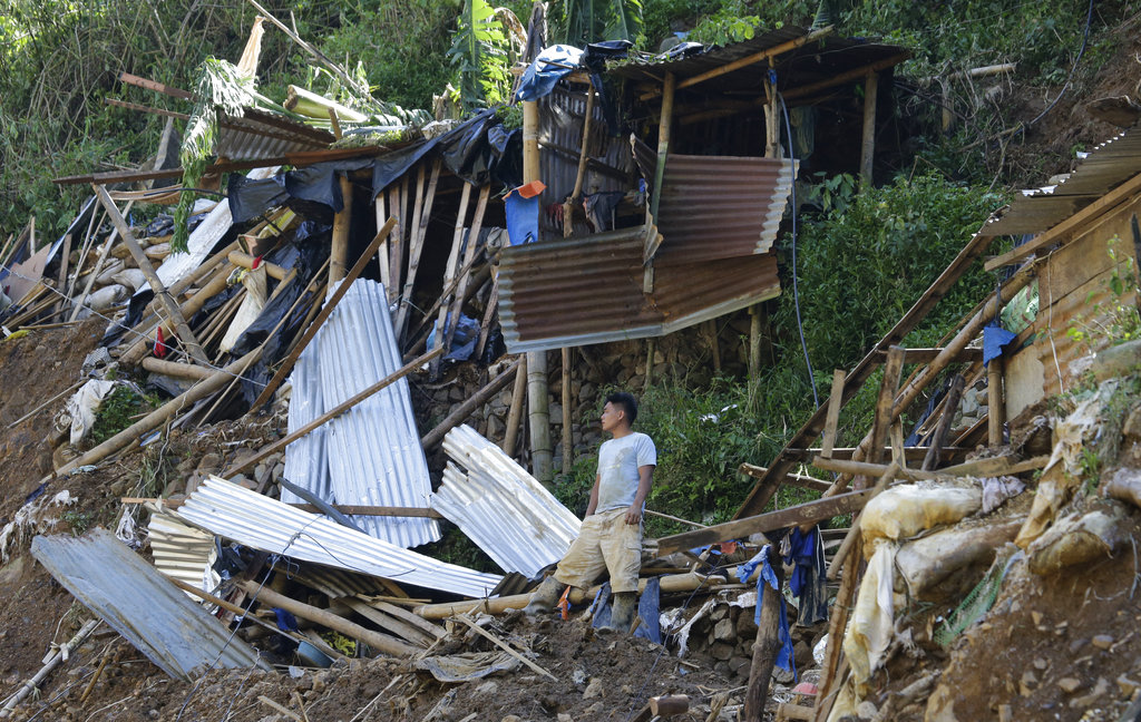 A resident stands beside toppled houses at the site where victims are believed to have been buried by a landslide after Typhoon Mangkhut lashed Itogon.