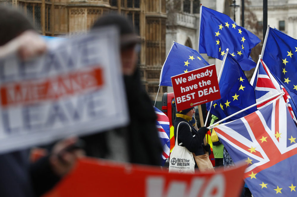 Pro- and anti-Brexit demonstrators wave their placards and flags outside the Houses of Parliament in London on Tuesday.