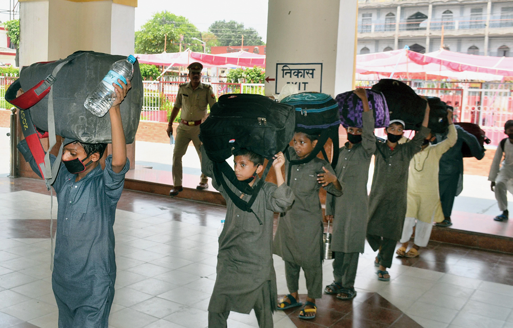 Children carry luggage as they enter a railway station in Moradabad on Saturday to travel home.