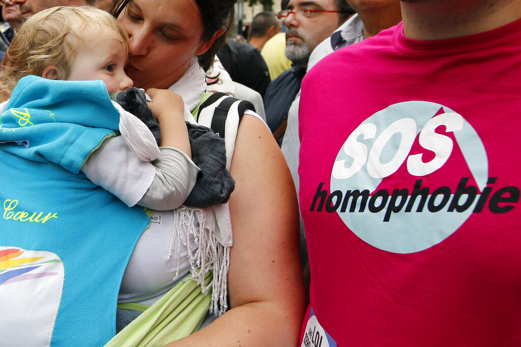 In this Saturday, June 28, 2014, file photo a woman kisses a baby next to a man wearing a shirt reading