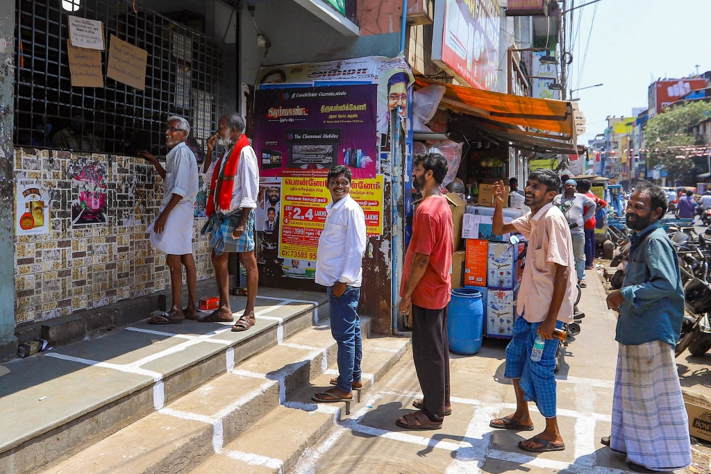 People maintain distance and stand in a queue to buy liquor from TASMAC outlet, in Chennai, on Saturday, March 21, 2020.
