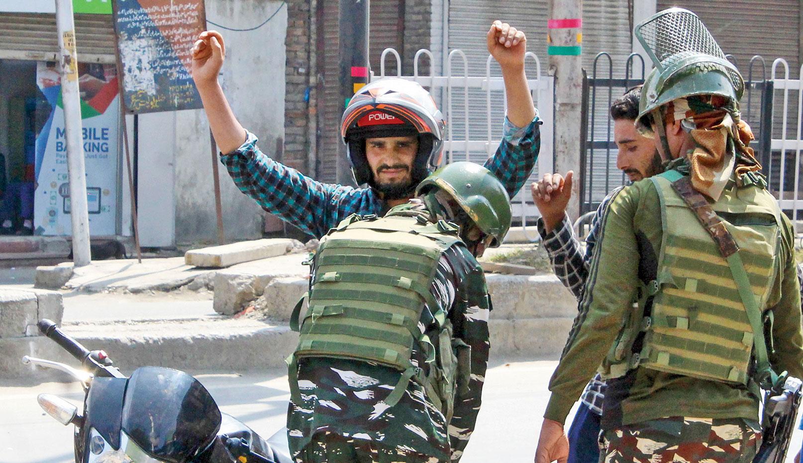 Security personnel frisk a biker in Srinagar on Sunday.