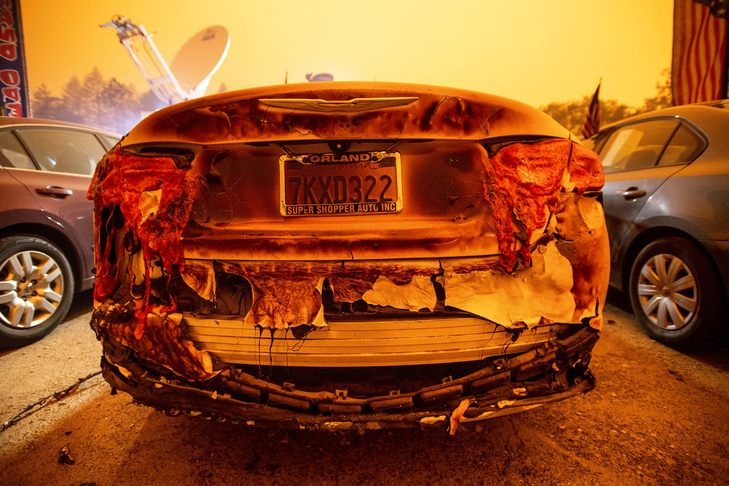 A scorched vehicle sits parked at a used car dealership in Paradise on Friday,