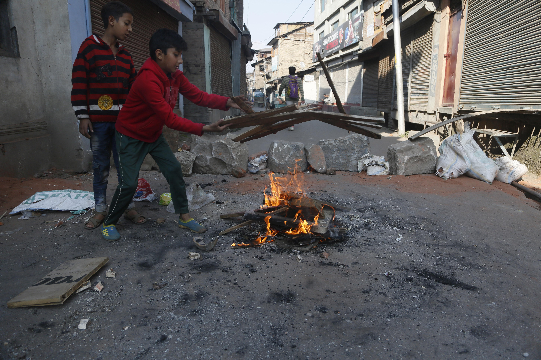 Young Kashmiri boys add wood to burn near a barricade in downtown Srinagar, Kashmir, on October 31, 2019