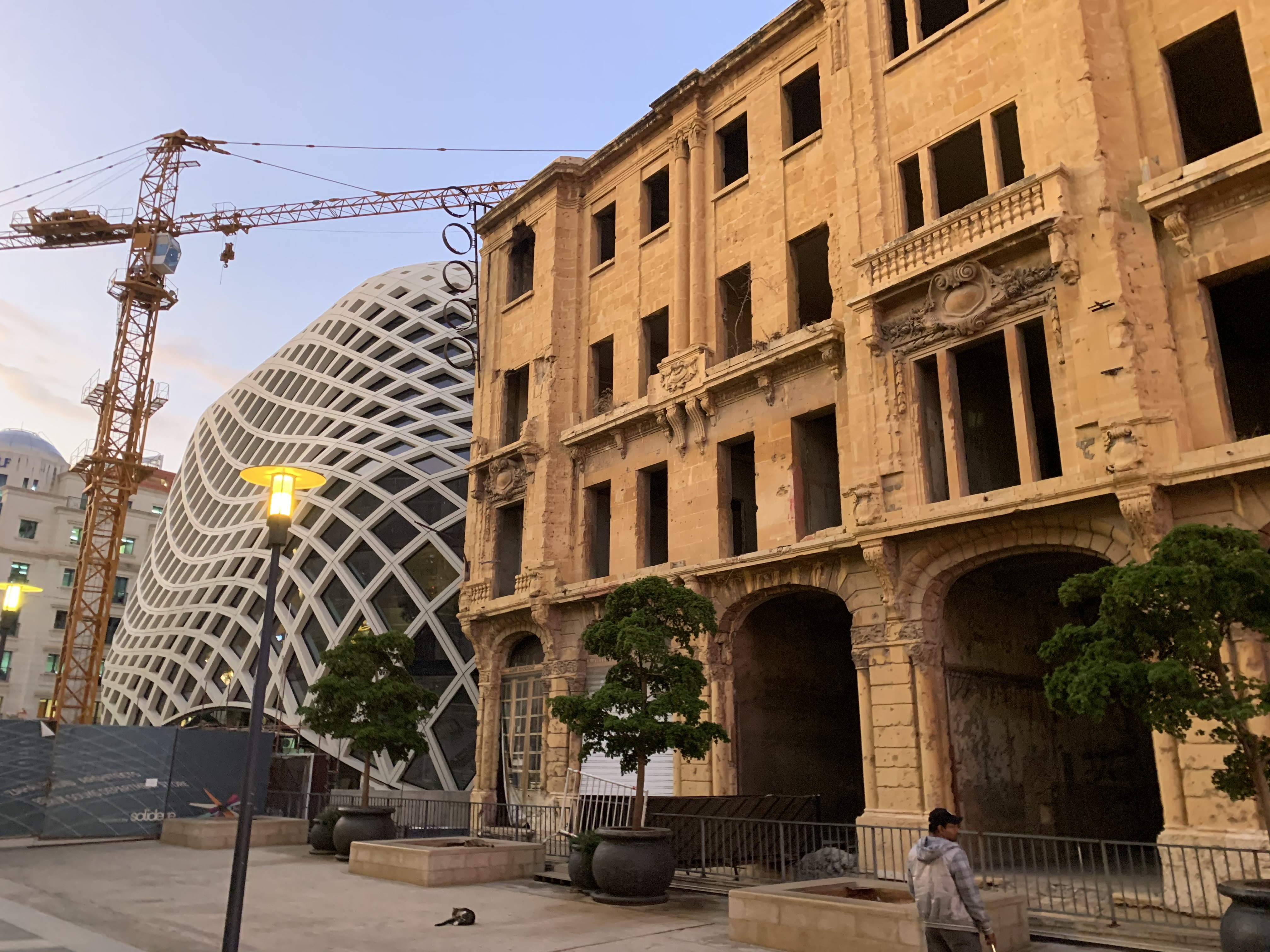 An old war-torn building standing next to a modern architectural marvel in downtown Beirut