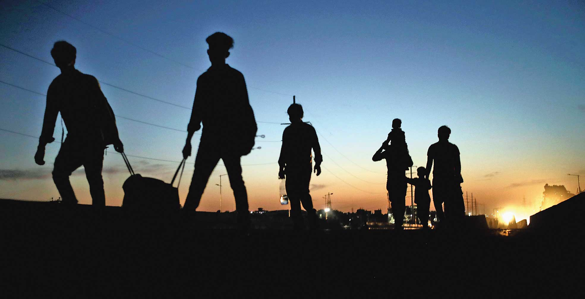 Migrant labourers and their family members are silhouetted as they leave New Delhi on March 28.