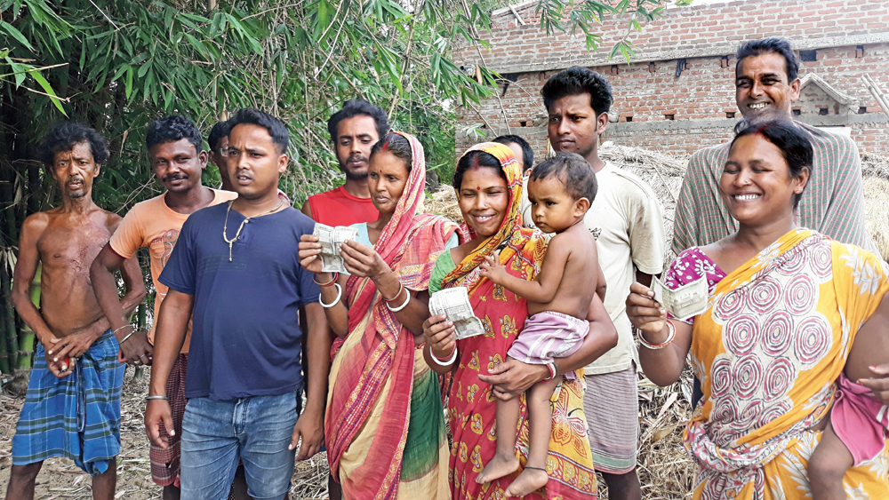 A group of villagers in Birbhum's Chhatra show currency notes they claim they received as cut money refunds from Trinamul leader Trilochan Mukherjee on Tuesday
