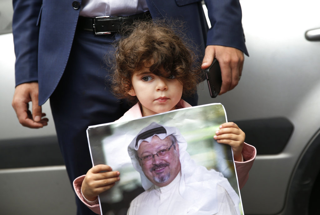 A girl holds a poster with a photo of Jamal Khashoggi during a protest near the Saudi consulate in Istanbul on Monday, October 9, 2018.
