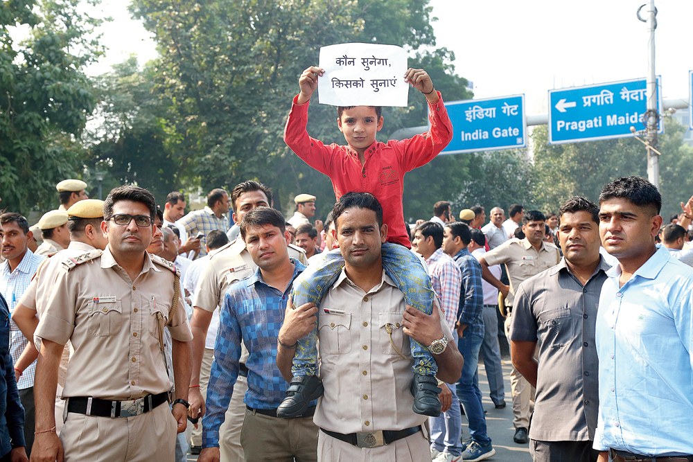 "Carried on the shoulders of a Delhi policeman outside the law-enforcement agency's headquarters in New Delhi on Tuesday, a child holds aloft a placard that asks: ""Who will hear us, who should we tell?"""
