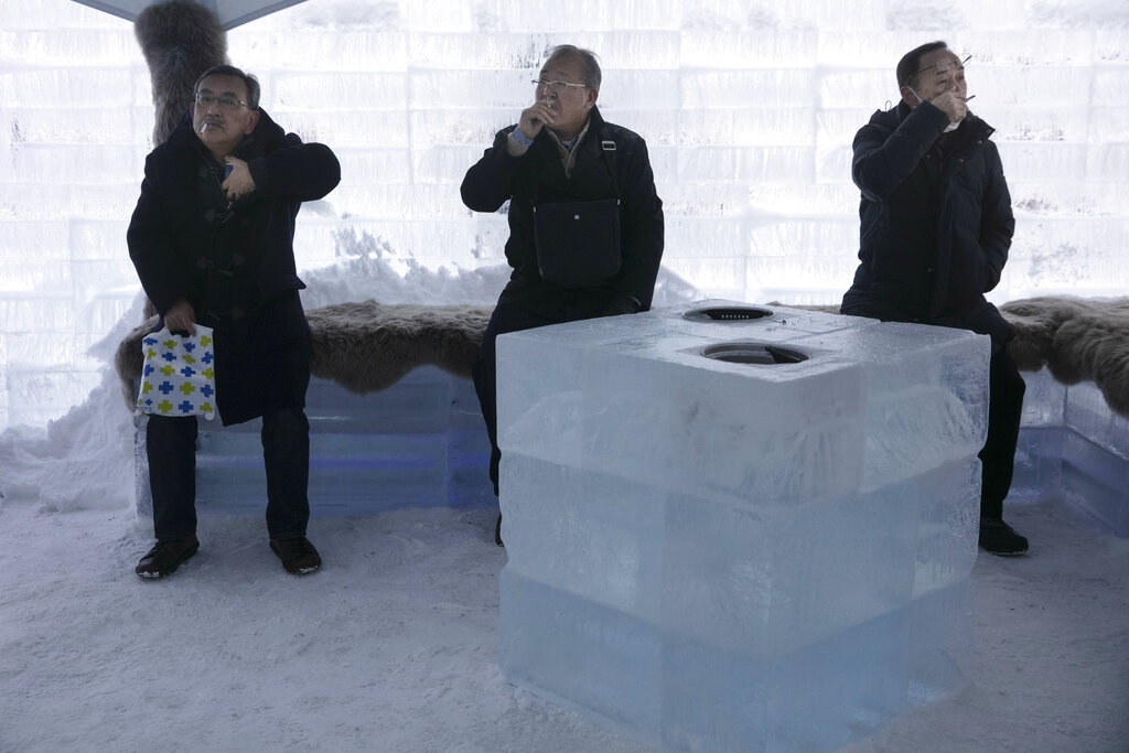 People smoke in a smoking room made with ice blocks at the annual Sapporo Snow Festival Tuesday