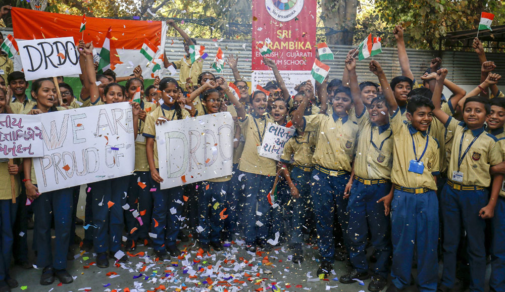 School students in Ahmedabad cheer as they hold flags and placards to celebrate the success of the Defence Research and Development Organisation's (DRDO's) Mission Shakti on Wednesday