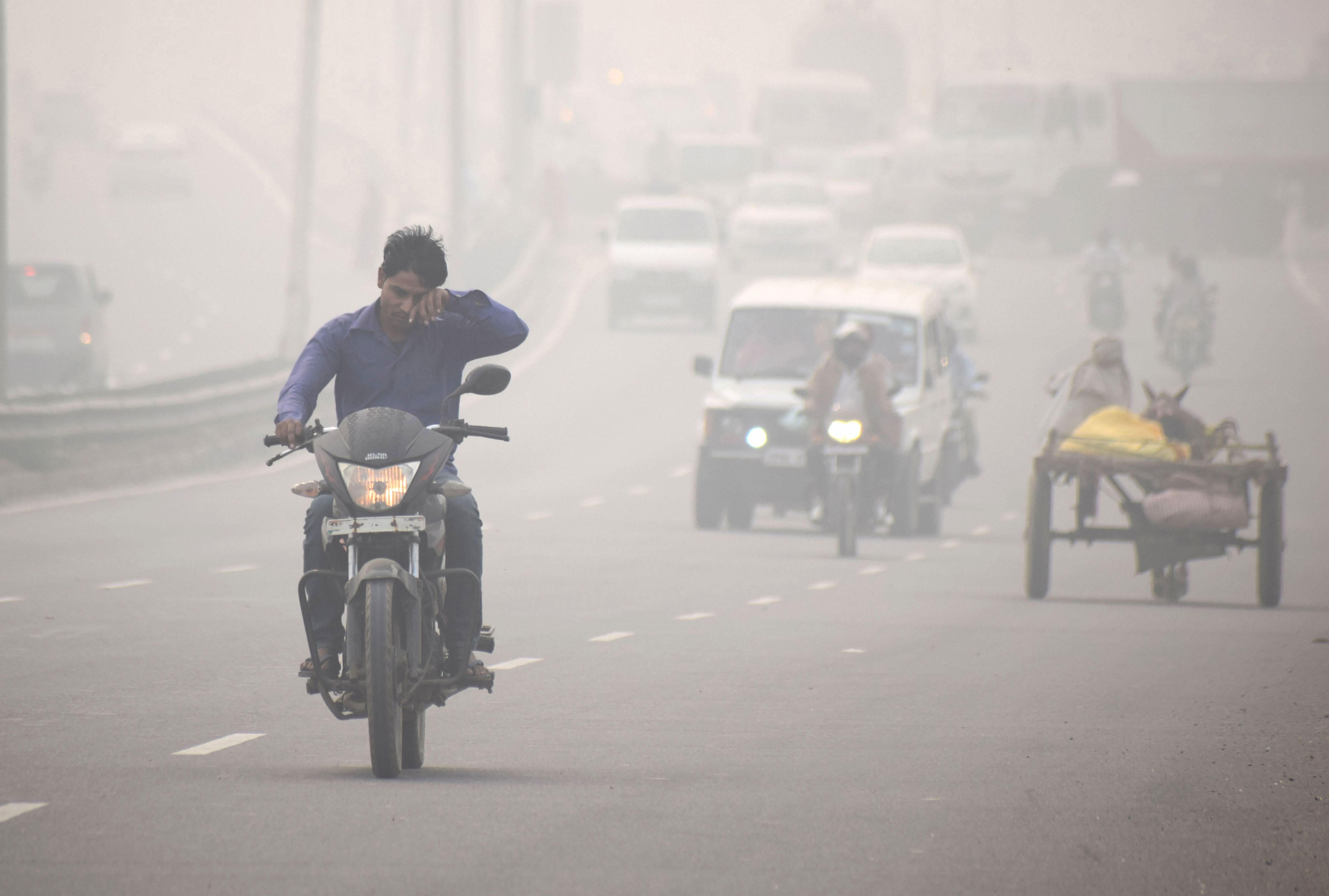 A motorcyclist rides through thick smog on NH-2, in Mathura, Sunday, November 03, 2019.