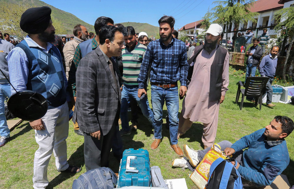 Election officials collect EVMs and other material for the first phase of Lok Sabha elections, at a distribution centre in Barmamulla district of north Kashmir on April 10, 2019
