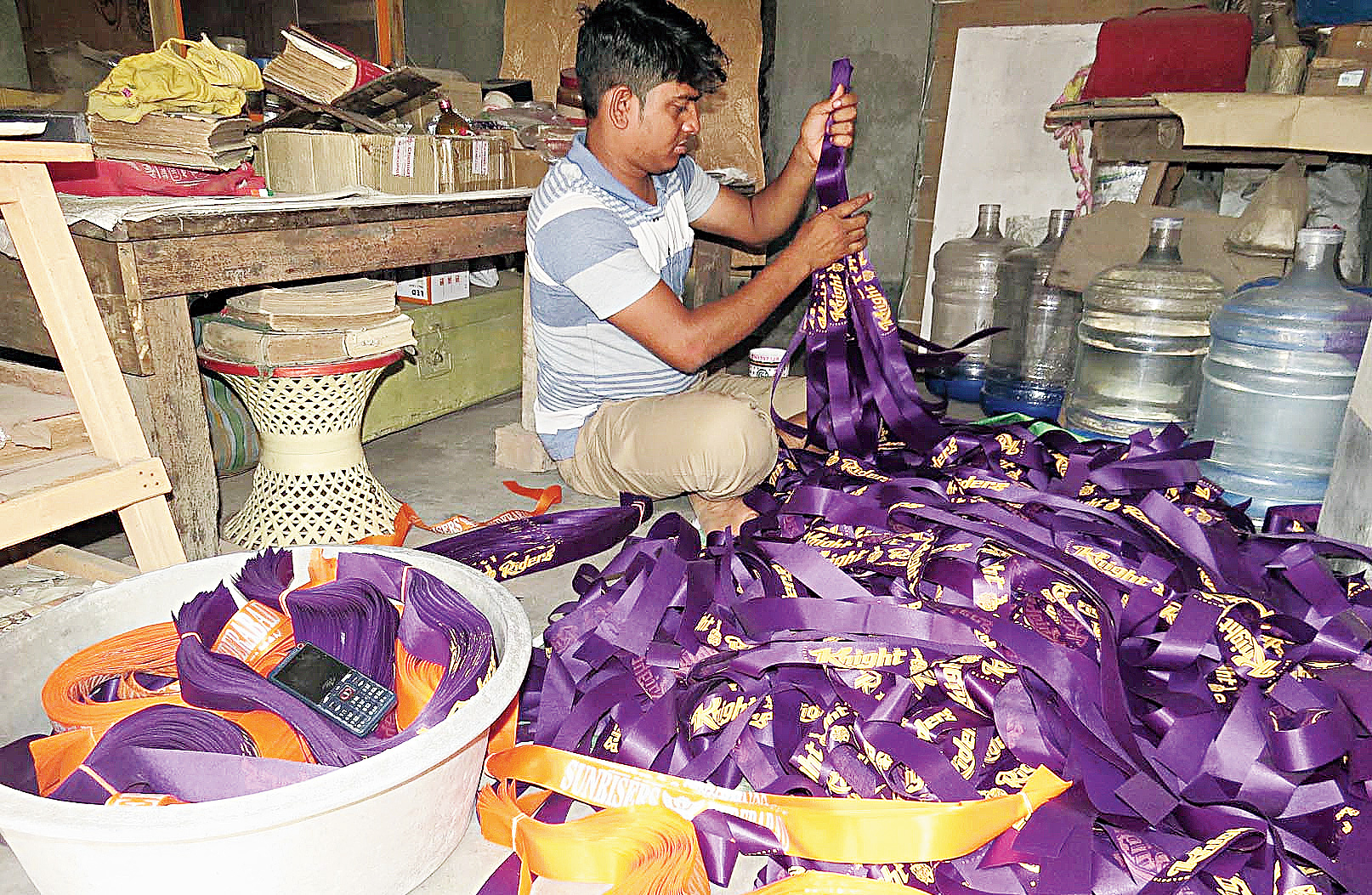 Manab Adhikari, who sells both in wholesale and retail, at work amid a pile of dyed purple headbands.
