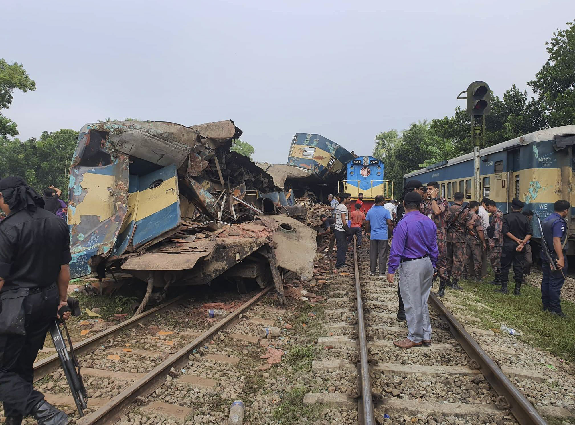 People gather near badly damages coaches after two speeding trains collided in in Brahmanbaria district, 82 kilometers (51 miles) east of the capital, Dhaka, Bangladesh, November 12, 2019