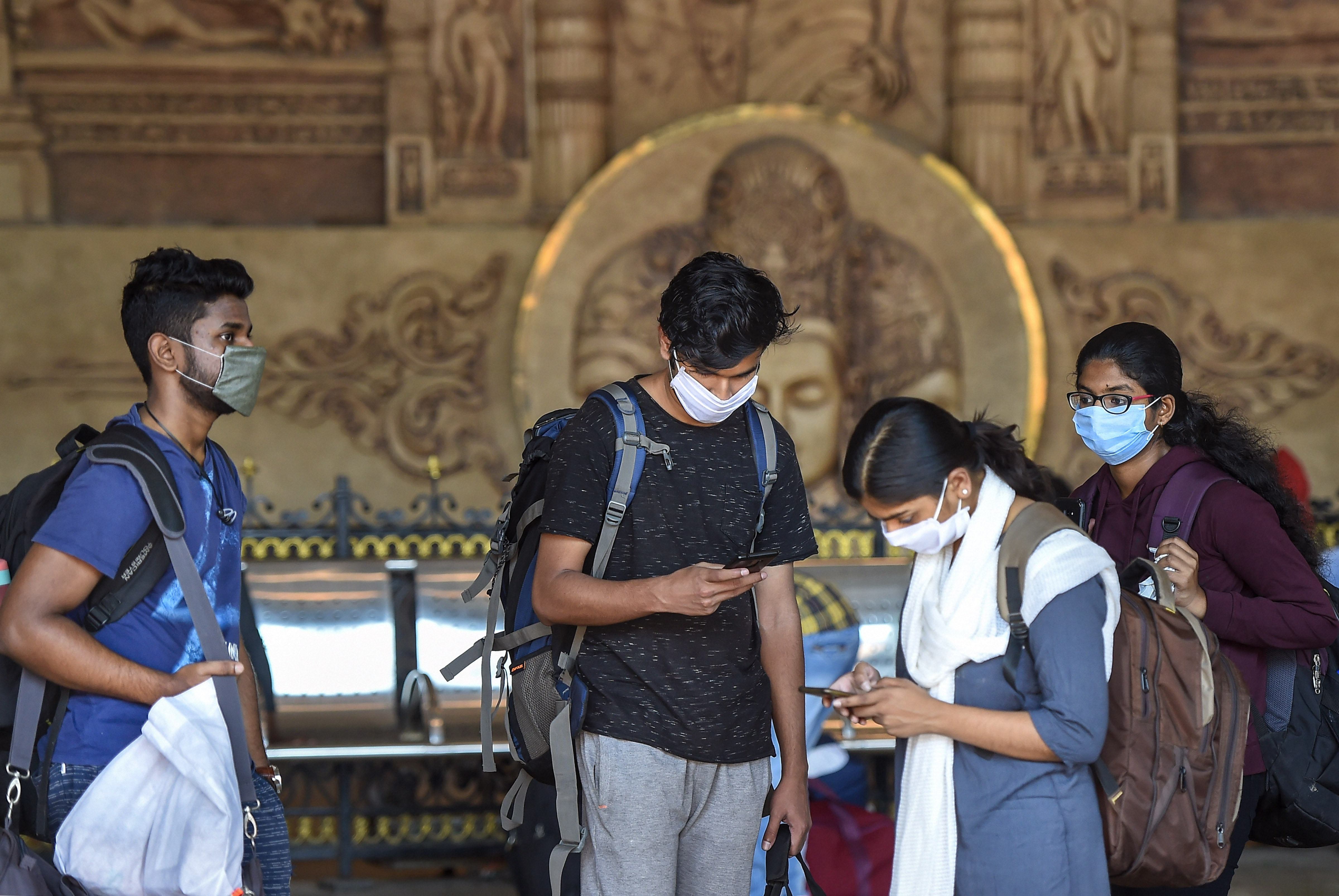 Passengers wear masks as a preventive measure against coronavirus, at Lokmanya Tilak Terminus in Mumbai, Tuesday, March 17, 2020