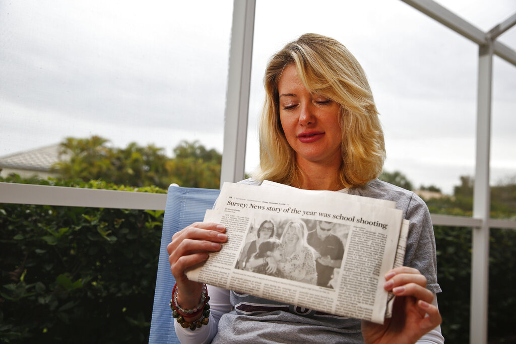 "Mechelle Boyle holds a newspaper with the iconic photo from the school shooting. ""The terror that we felt, I see it on my face every time I look at the picture,"" she said."