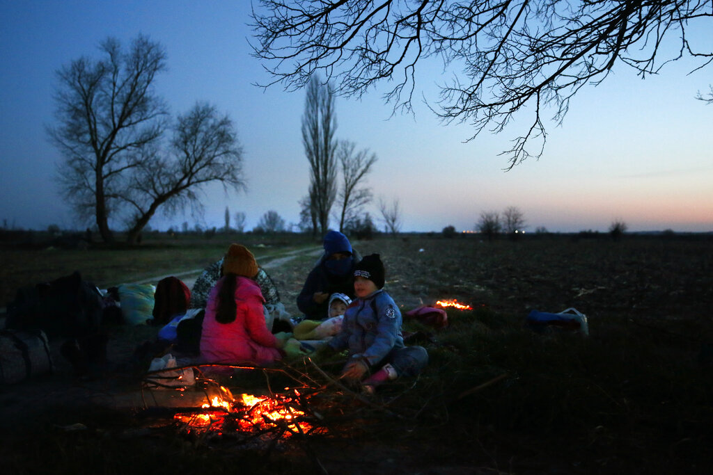 A group of migrants spend the night near the border crossing at the Pazarakule gate near Edirne, at the Turkish-Greek border on Monday, on March 2, 2020. Thousands of migrants and refugees massed at Turkey's western frontier, trying to enter Greece by land and sea after Turkey said its borders were open to those hoping to head to Europe.