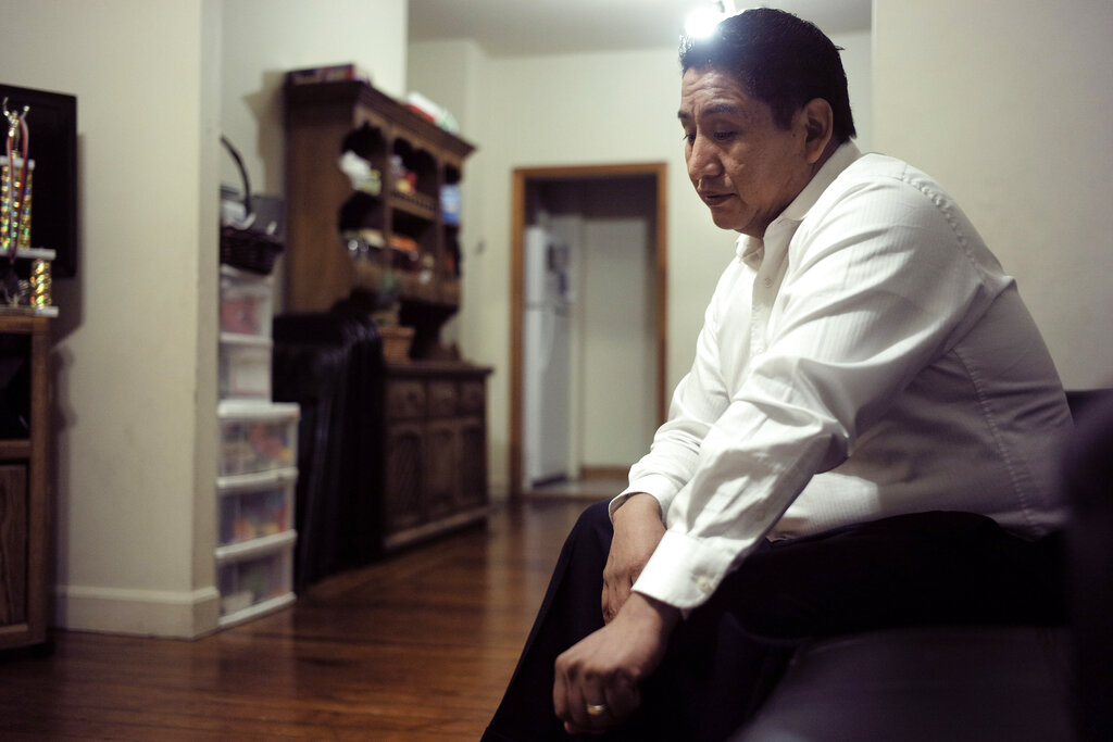 """In this Thursday, Novomber 21, 2019 photo Audencio Lopez, a 39-year-old native of Guatemala, is interviewed by a reporter from The Associated Press at his home in Lynn, Massachusetts. After going through the immigration court process for seven years, Lopez was told at a court hearing this past fall that the government won't oppose granting him a visa due to his """"exemplary"""" record and community service. But Lopez admits the family's joy is tempered by uncertainty because his wife's immigration status remains unresolved."""