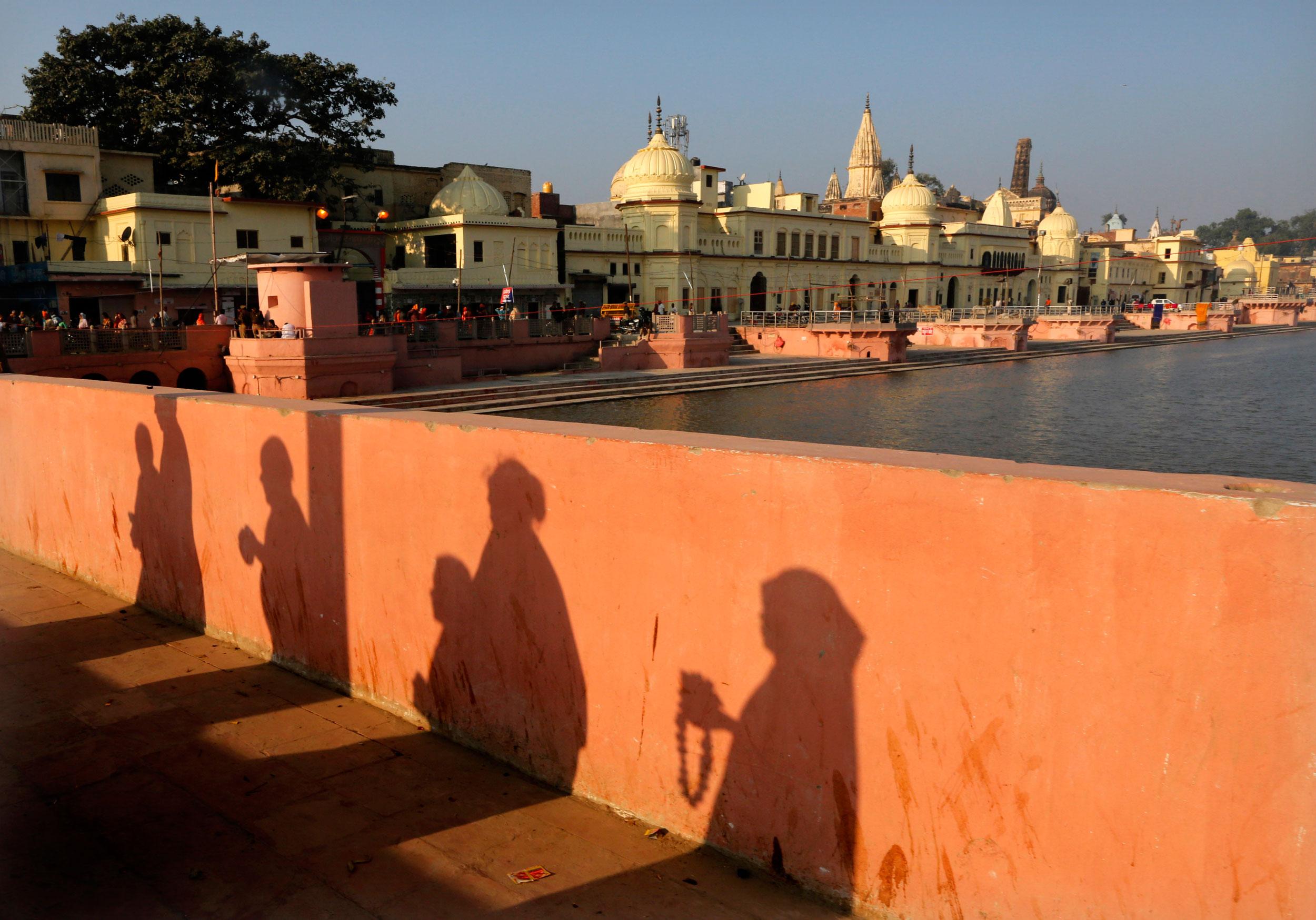 Hindu devotees pray while walking towards a temple in Ayodhya on November 11, 2019.