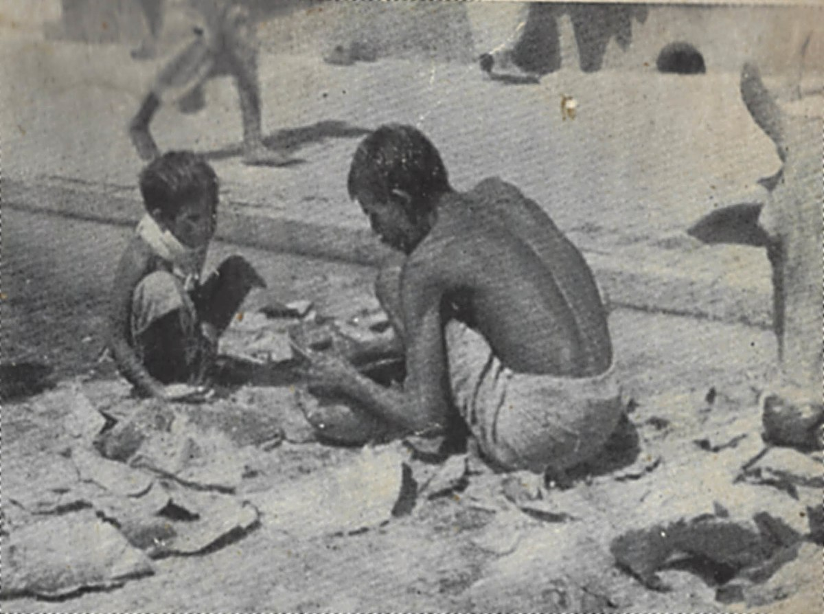 A boy, his father, and a cow rummage for scraps on a street during the Bengal famine of 1943