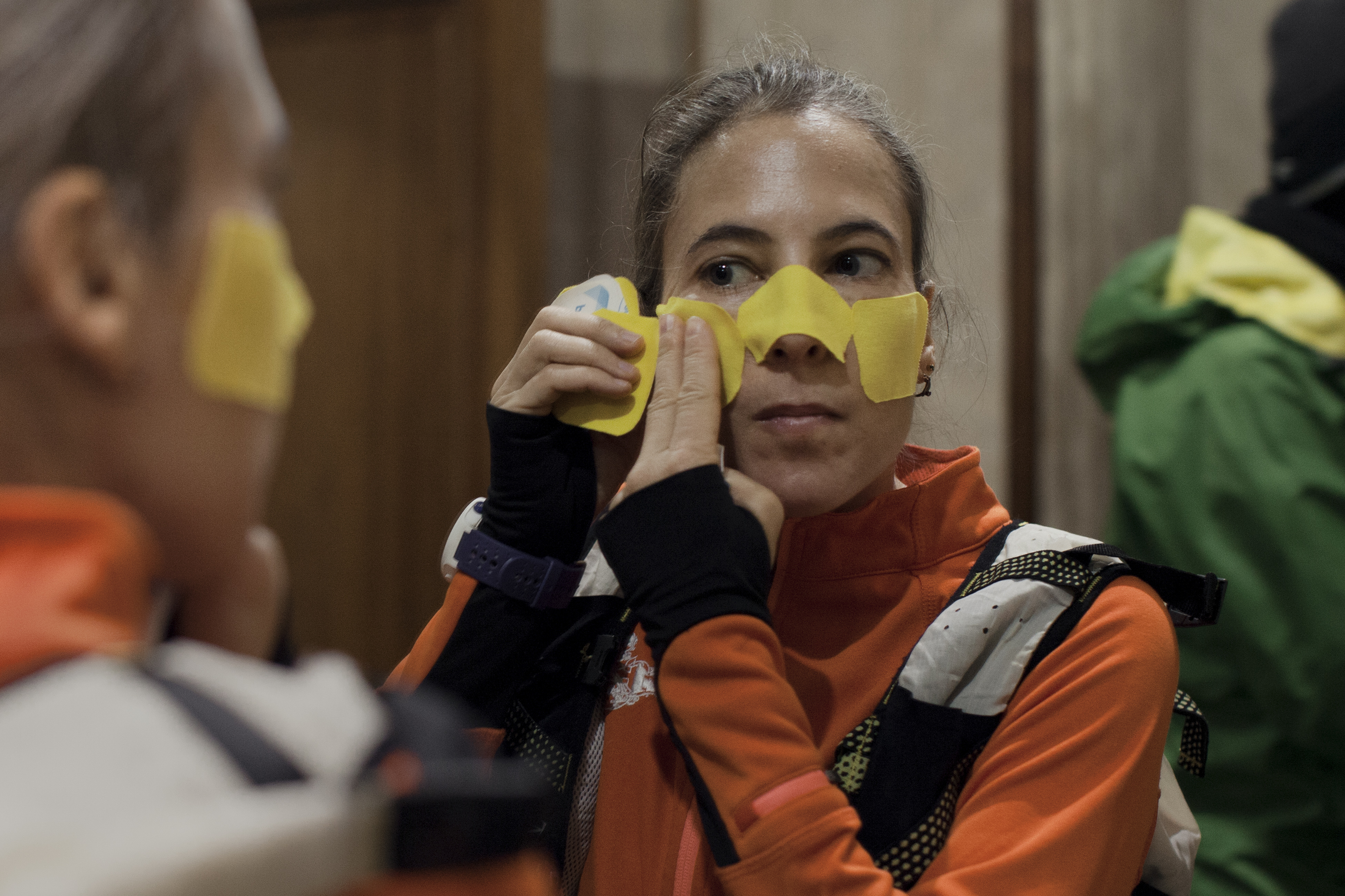 Véronique Messina, a runner from France, attaches athletic tape to protect her face from frostbite, on the morning of the Baikal Ice Marathon.