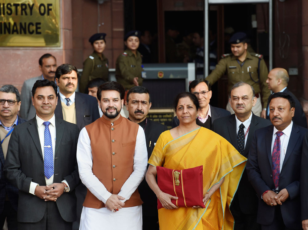 Finance Minister Nirmala Sitharaman, holding a folder containing the Union Budget documents, poses for photographers along with her deputy Anurag Thakur (in brown Nehru jacket), Chief Economic Adviser Krishnamurthy Subramanian (in blue tie) and a team of officials