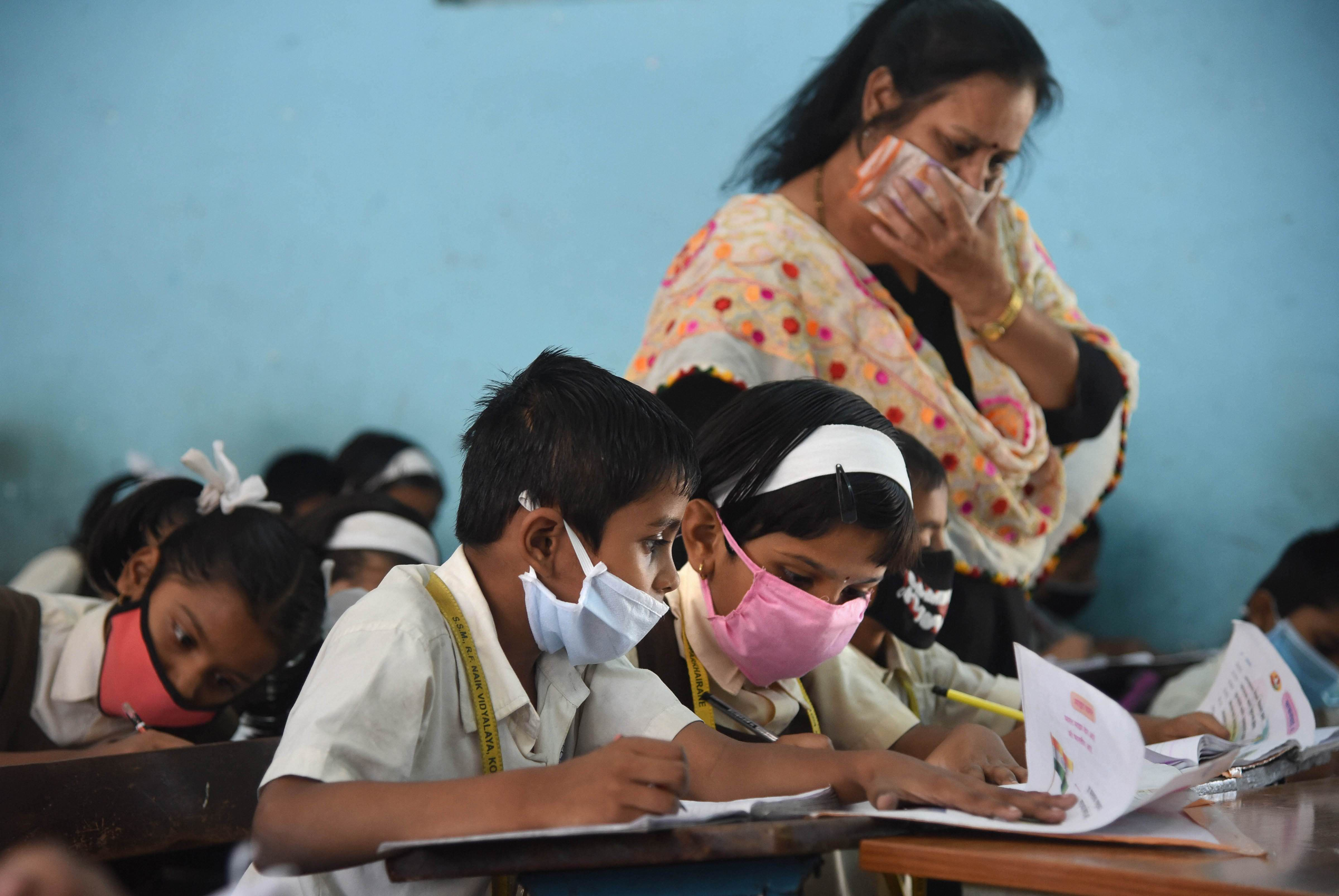 Students wearing masks in view of coronavirus pandemic attend a class, in Navi Mumbai, Saturday, March 14, 2020