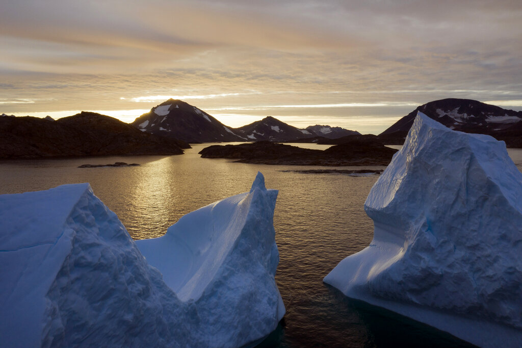 This August 16, 2019, file photo shows an aerial view of large icebergs floating as the sun rises near Kulusuk, Greenland. Greenland has been melting faster in the last decade, and this summer, it has seen two of the biggest melts on record since 2012.