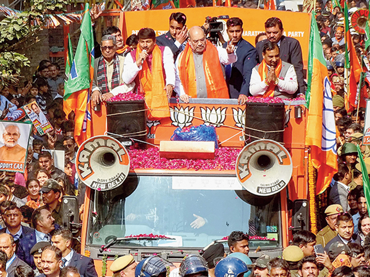 """Home minister Amit Shah at a poll roadshow at Ghonda in Delhi on January 26. A section of the crowd at this roadshow was heard chanting: """"Desh ke gaddaron ko, goli maaro...."""" (Shoot the traitors) The phrase """"Aap chronology samajh lijiye"""" (understand the chronology) became famous after Shah used it at a Bengal meeting to explain the link between the Citizenship Amendment Act and the National Register of Citizens"""